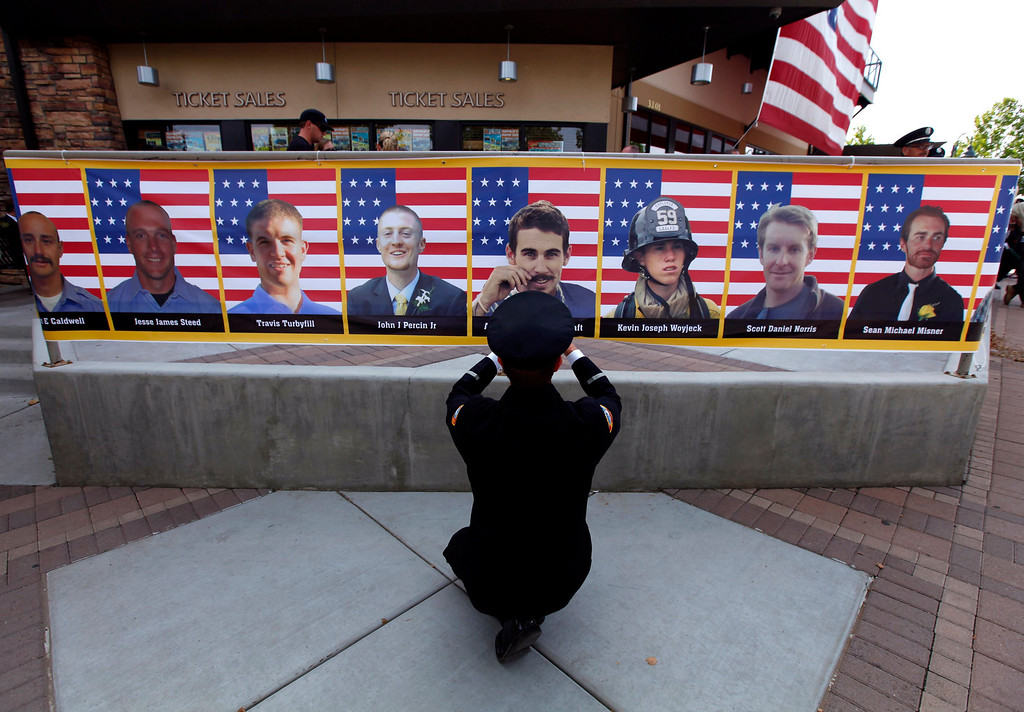 . San Diego firefighter Robert Bunsoldat takes a picture of each of the Prescott Fire Department\'s Granite Mountain Hotshots team from a banner that circles the entrance to their memorial in Prescott Valley, Arizona July 9, 2013. REUTERS/Mike Blake