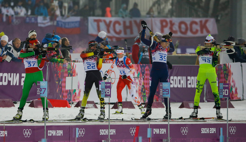 . Belarus\' Liudmila Kalinchik, Germany\'s Andrea Henkel, Norway\'s Synnoeve Solemdal and Slovakia\'s Jana Gerekova, from left, shoot as Poland\'s Krystyna Palka, background, arrives at the shooting range during the women\'s biathlon 10k pursuit, at the 2014 Winter Olympics, Tuesday, Feb. 11, 2014, in Krasnaya Polyana, Russia. (AP Photo/Gero Breloer)