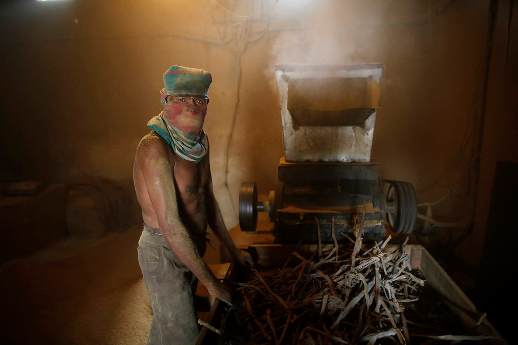 """. A worker crushes locally grown tobacco in a grinding machine in a small \'bidi\' (cigarette) factory at Haragach in Rangpur district, Bangladesh July 11, 2013. According to a 2012 study by US-based NGO, Campaign for Tobacco-Free Kids, over 45,000 people in Bangladesh are employed in manufacturing inexpensive cigarettes known as bidis and this number includes \""""many women and children working in household based establishments where they make low wages and live in poverty.\"""" A 2011 research paper about bidi workers in Bangladesh, published in the journal Tobacco Control, says that working conditions can involve poor ventilation and exposure to tobacco dust, which can cause a range of health problems including respiratory and skin diseases. International attention has been focused on workers\' safety in Bangladesh since the disaster at Rana Plaza, a garment factory complex which collapsed in April, killing 1,132 workers.   REUTERS/Andrew Biraj"""