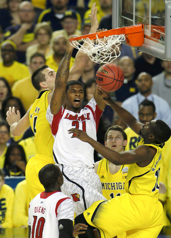 . Louisville Cardinals forward Chane Behanan (C) dunks the ball between Michigan Wolverines forward Mitch McGary (L) and guard Tim Hardaway Jr. (R) in their NCAA men\'s Final Four championship basketball game in Atlanta, Georgia April 8, 2013. REUTERS/Tami Chappell