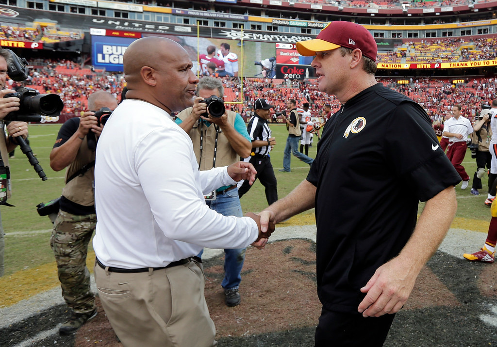 . Cleveland Browns head coach Hue Jackson, left, and Washington Redskins head coach Jay Gruden meet at midfield after an NFL football game Sunday, Oct. 2, 2016, in Landover, Md. (AP Photo/Chuck Burton)