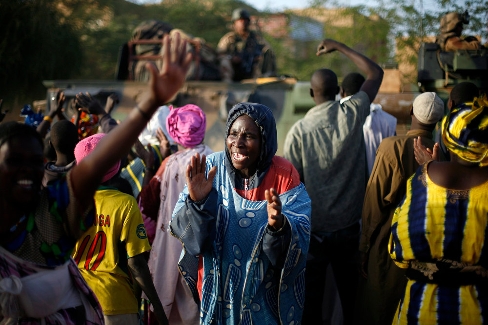 . A Malian women cheers Malian soldiers arriving in a convoy at the military base in Timbuktu, Mali, Saturday Feb. 2, 2013. French President Francois Hollande visited the fabled city for two hours, twenty days after the start of operation Serval. (AP Photo/Jerome Delay)