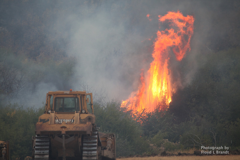 Havre Daily News/Floyd Brandt   Bulldozers attaches the fire as it flares up at Sucker Creek Road Thursday