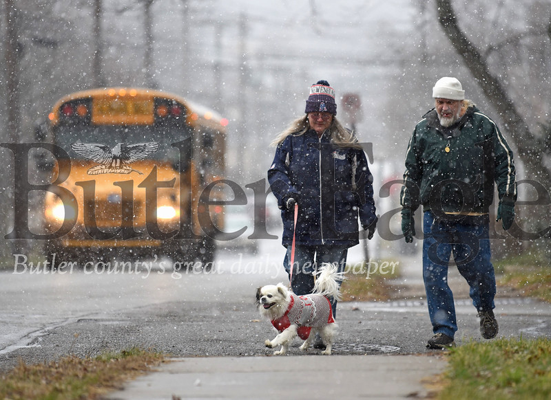 Steven Hartwick (right) and Annee Burk of Butler walk their dog Brady down West Brady St. Thursday afternoon as snow showers began to move into the county. Burk, originally a Boston area native, said their dog was not named after the Butler street they live on, but rather a certain New England quarterback. Seb Foltz/Butler Eagle