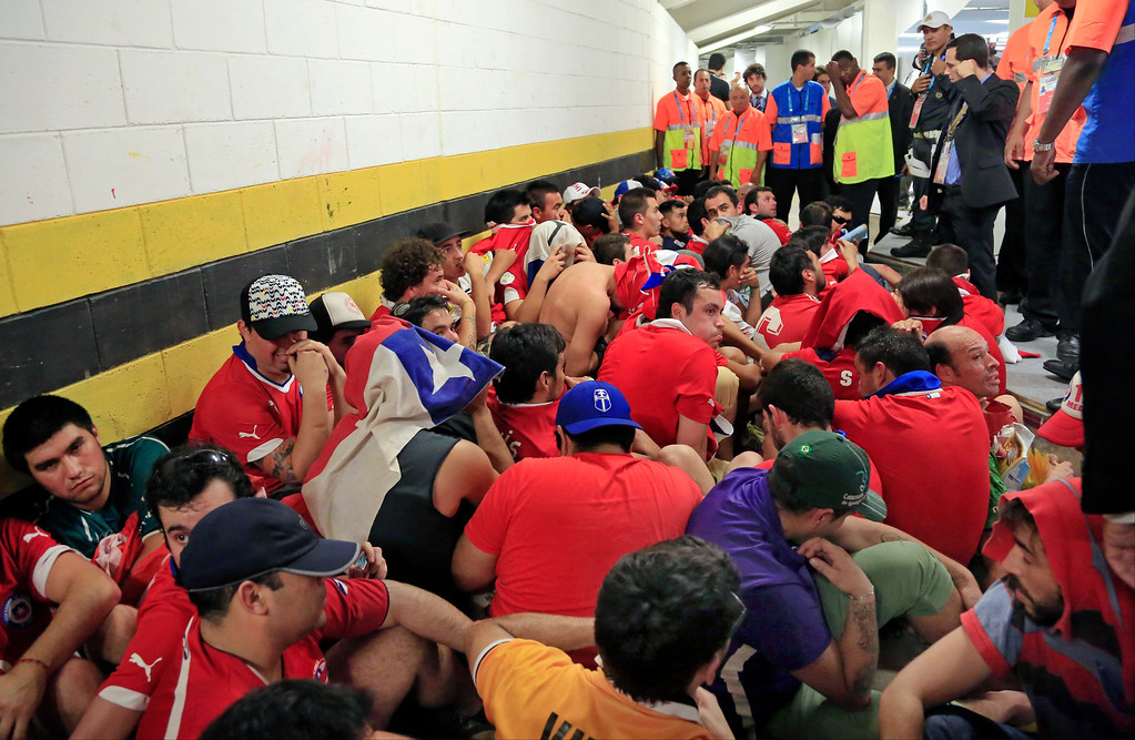 . Chilean fans are surrounded by security personnel after breaking into Maracana Stadium before the group B World Cup soccer match between Spain and Chile in Rio de Janeiro, Brazil, Wednesday, June 18, 2014.  (AP Photo/Bernat Armangue)