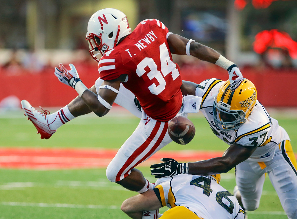 . Nebraska running back Terrell Newby (34) fumbles the ball as he is tackled by Southern Mississippi defensive lineman Wil Freeman (46) and linebacker Alan Howze (37) in the second half of an NCAA college football game in Lincoln, Neb., Saturday, Sept. 7, 2013. Nebraska won 56-13. (AP Photo/Nati Harnik)