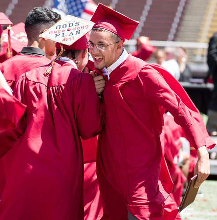 06/19/18 Wesley Bunnell | Staff A New Britain High School senior shakes hands with a friend as he walks down the aisle to his seat after receiving his diploma during graduation exercises at Veterans' Memorial Stadium at Willow Brook Park on Tuesday morning.