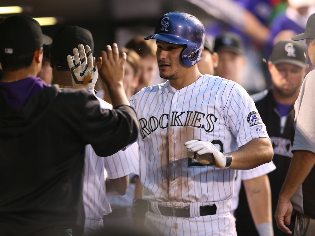 . Colorado Rockies\' Nolan Arenado, front right, is congratulated after hitting a solo home run against the Pittsburgh Pirates in the seventh inning of the Rockies\' 8-1 victory in a baseball game in Denver, Saturday, July 26, 2014. (AP Photo/David Zalubowski)