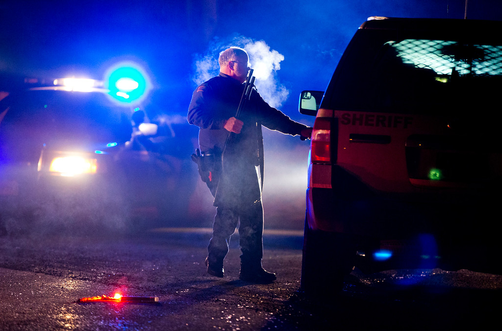 . A Oregon State police officer stands by a vehicle as police officers block Highway 395 in Seneca, Ore., Tuesday, Jan. 26, 2016. Authorities said shots were fired Tuesday during the arrest of members of an armed group that has occupied a national wildlife refuge in Oregon for more than three weeks. (Dave Killen/The Oregonian via AP)
