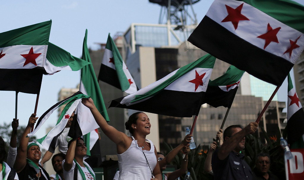 . Protesters shout slogans against Syria\'s President Bashar al-Assad as they wave Syrian opposition flags during a protest marking two years since the start of the uprising, at Avenida Paulista in Sao Paulo March 15, 2013. REUTERS/Nacho Doce