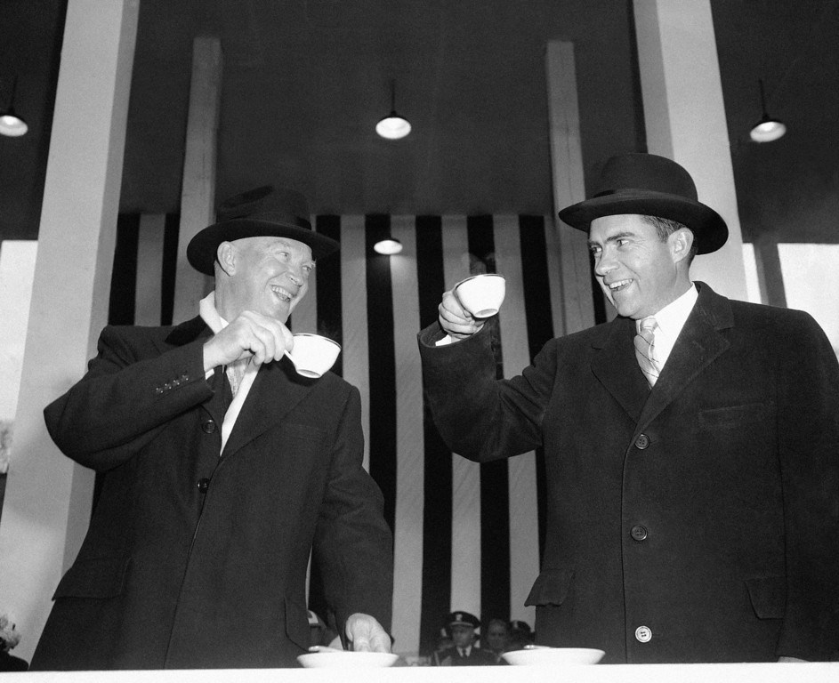 . President Dwight Eisenhower and Vice President Richard Nixon appear to be toasting one another as they exchange smiles over cups of hot coffee in reviewing stand during inaugural parade in Washington, Jan. 21, 1957. (AP Photo)