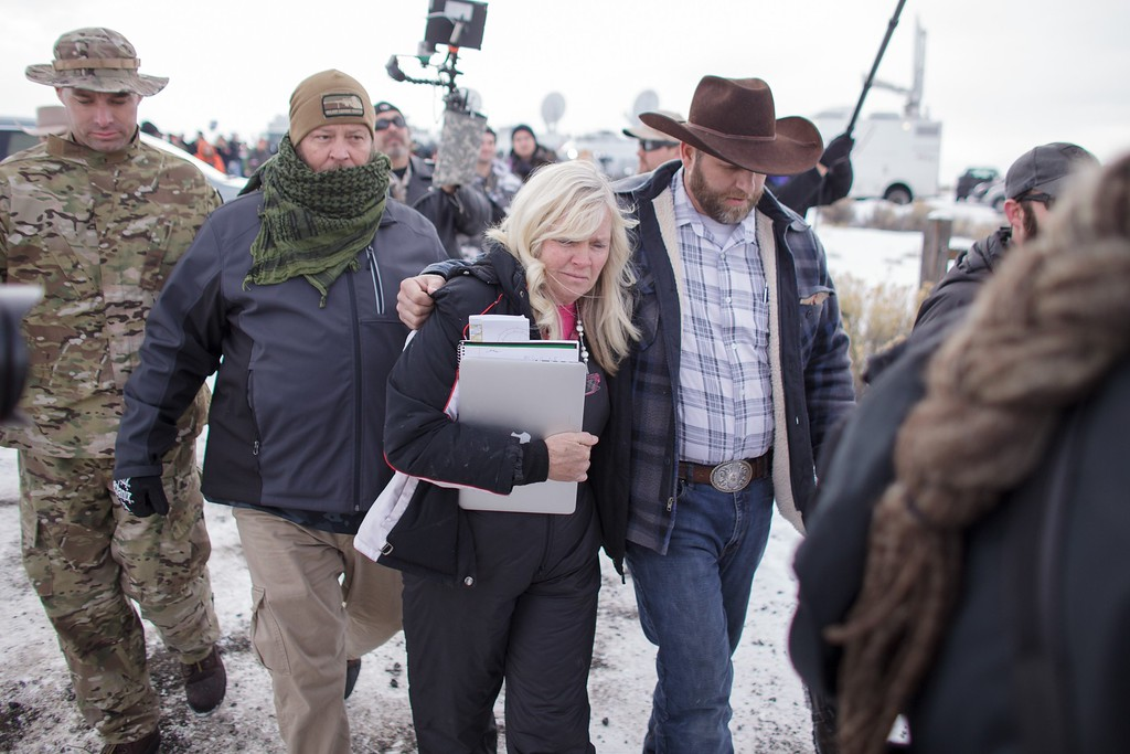 . Ammon Bundy(R), leader of a group of armed anti-government protesters leaves with Shawna Cox(C), after speaking to the media as other members look on at the Malheur National Wildlife Refuge near Burns, Oregon January 4, 2016. The FBI on January 4 sought a peaceful end to the occupation by armed anti-government militia members at a US federal wildlife reserve in rural Oregon, as the standoff entered its third day. The loose-knit band of farmers, ranchers and survivalists -- whose action was sparked by the jailing of two ranchers for arson -- said they would not rule out violence if authorities stormed the site, although federal officials said they hope to avoid bloodshed. AFP PHOTO / ROB KERRROB KERR/AFP/Getty Images
