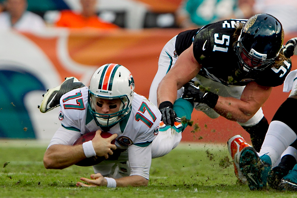 Description of . Miami Dolphins quarterback Ryan Tannehill (17) dives past Jacksonville Jaguars linebacker Paul Posluszny (51) for a first down during the second quarter of an NFL football game, Sunday, Dec. 16, 2012, in Miami. The Dolphins won 24-3. (AP Photo/The Miami Herald, Joe Rimkus Jr.)