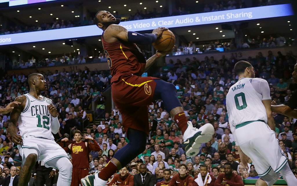 . Cleveland Cavaliers forward LeBron James, center, recoils after colliding with Boston Celtics forward Jayson Tatum, right, in front of Celtics guard Terry Rozier, left, during the first half in Game 2 of the NBA basketball Eastern Conference finals Tuesday, May 15, 2018, in Boston. (AP Photo/Charles Krupa)