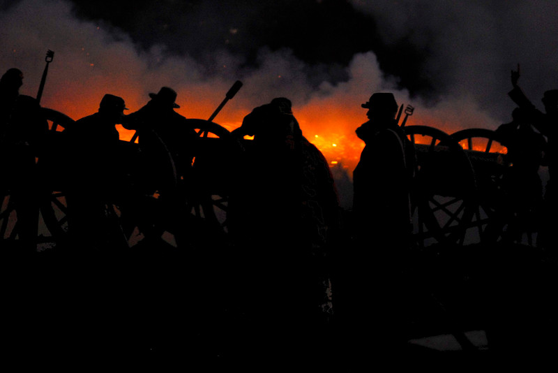 Artillery members are silhouetted against the sparks of artillery fire during a nighttime demonstration at Patriots Point in Mt. Pleasant, South Carolina on Tuesday, April 12, 2011. ..The 150th Anniversary of the Firing on Ft. Sumter was commemorated with lectures, performances, demonstrations, and a living history throughout the area on James Island, Charleston, Mt. Pleasant, and Sullivan's Island during the week from April 8-14, 2011. Photo Copyright 2011 Jason Barnette