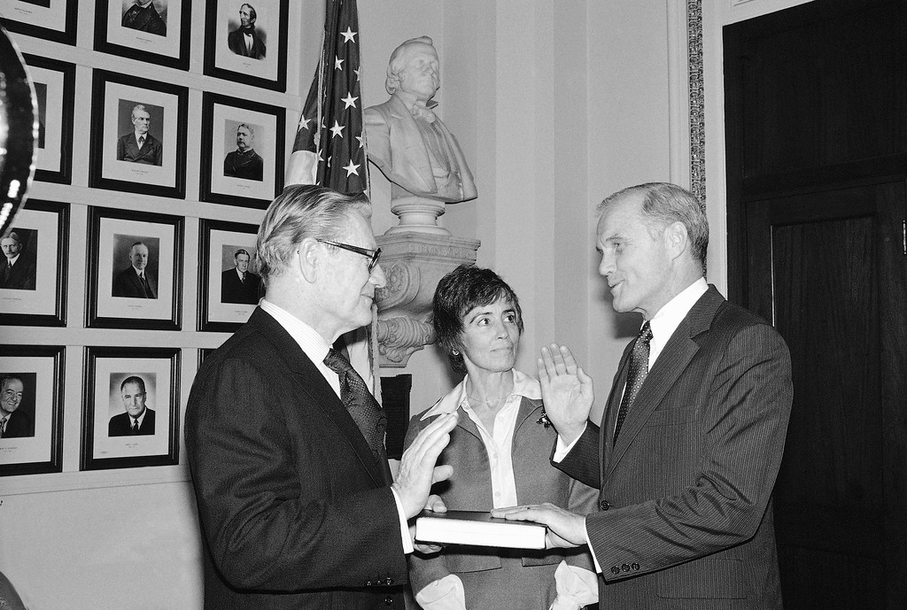 . Vice-President Nelson Rockefeller, left, swears in Sen. John Glenn, R-Ohio, in this re-enactment at the Capitol in Washington, Tuesday, Jan. 14, 1975. Glenn\'s wife Anna is at center. (AP Photo)