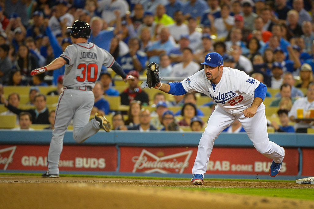 . Dodger\'s Adrian Gonzalez gets Atlanta\'s Elliot Johnson out at first on a throw from Juan Uribe during game action Monday, October 7, 2013 ( Photo by Andy Holzman/Los Angeles Daily News )