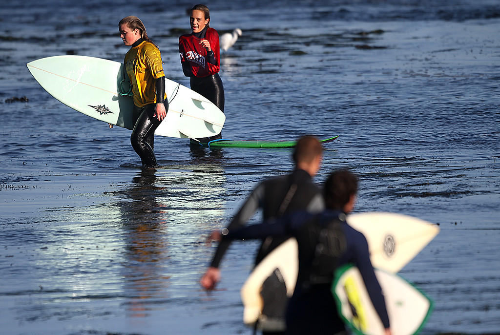 . Competitors exit the water after the women\'s shortboard final at Pleasure Point in Capitola, Calif., during the Santa Cruz Scholastic Surf League contest Sunday, Feb. 24, 2013. (Jon Weiand/Santa Cruz Sentinel Sentinel)