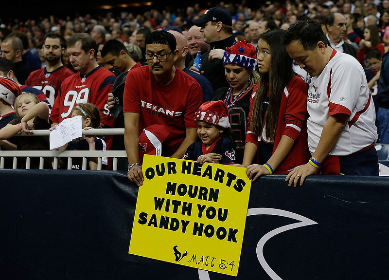 . Houston Texans fans take a moment to remember the victims of a massacre at Sandy Hook Elementary School in Newtown, Connecticut prior to the start of the game against the Indianapolis Colts at at Reliant Stadium on December 16, 2012 in Houston, Texas.  (Photo by Scott Halleran/Getty Images)