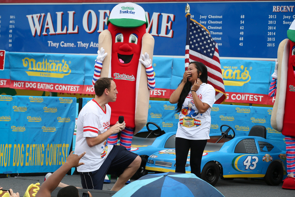 . Competitive eater Joey Chestnut proposes to his girlfriend and fellow competitor Neslie Ricasa before the Nathan\'s Famous Fourth of July International Hot Dog Eating contest at Coney Island, Friday, July 4, 2014, in New York. Chestnut won his competition and eighth consecutive contest by finishing 61 hot dogs and buns. (AP Photo/John Minchillo)