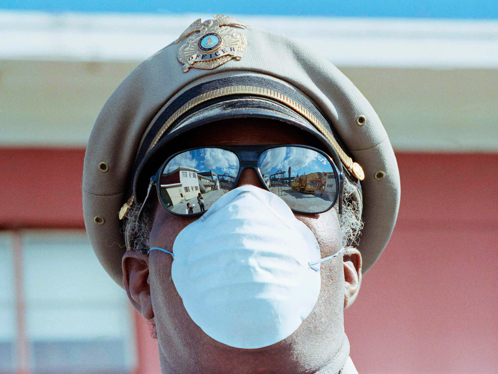 . The demolition of the I-880 Cypress structure and its dangerous proximity to the residences of West Oakland are mirrored in the glasses of Oakland Housing Authority police officer Price Holbert who wears a fiber mask to protect him from heavy dust, Oct. 26, 1989, Oakland, Calif.  (AP Photo/Paul Sakuma)
