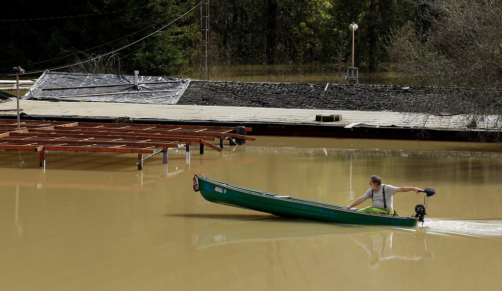 . A man operates a motor boat in a flooded area Friday, Feb. 10, 2017, in Guerneville, Calif. The Russian River rose above its flood stage again on Friday due to excessive rain in the area causing minor flooding. (AP Photo/Ben Margot)