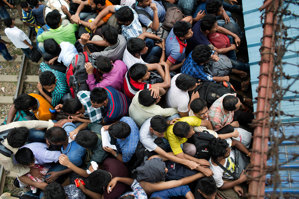 . Bangladeshi Muslims sit on the roof of an overcrowded train to travel home for Eid al-Fitr celebrations, at a railway station in Dhaka, Bangladesh, Thursday, June 14, 2018. Hundreds of thousands of people working in Dhaka are leaving for their hometowns to celebrate the upcoming Eid al-Fitr with their families. (AP Photo/A.M. Ahad)