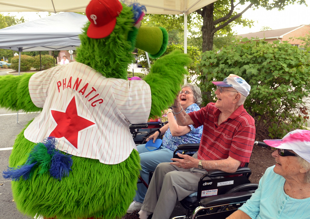 . The Philly  Phanatic delivers high-fives on his  visit to the Fifth Annual Senior Olympics held at Dock Terrace in Towamencin.   The Phanatic also made a guest appearance as a pitcher and cheeleader during the residents\' baseball game.  Youngsters from nearby Salford Mennonite Childcare Center also joined the game. Thursday, August 21, 2014.   Photo by Geoff Patton