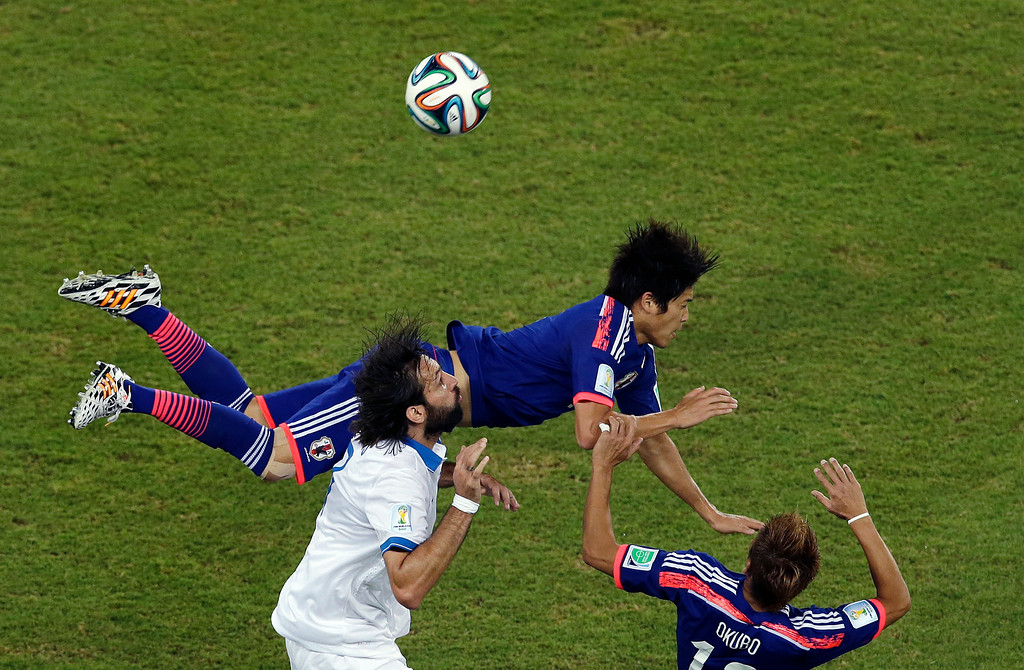 . Greece\'s Giorgos Samaras, left, challenges for the ball with Japan\'s Atsuto Uchida, top, and Yoshito Okubo during the group C World Cup soccer match between Japan and Greece at the Arena das Dunas in Natal, Brazil, Thursday, June 19, 2014. (AP Photo/Hassan Ammar)