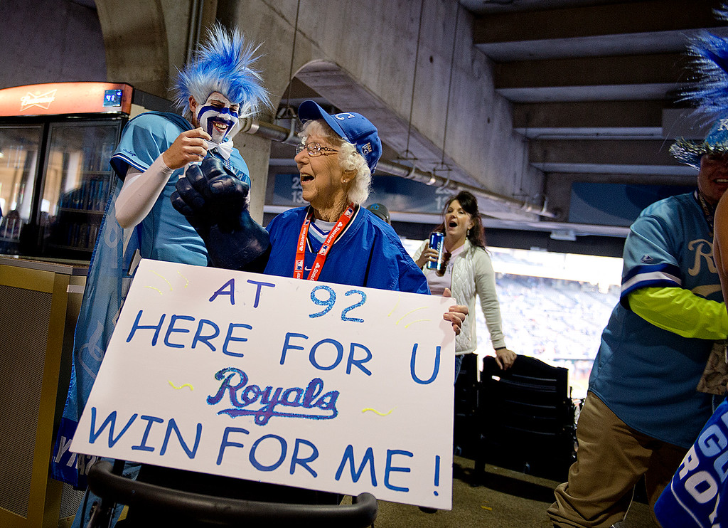 . Kris Stone, left fist bumps 92 year-old Lorraine Hawkins of Joplin, Mo. before Game 6 of the World Series at Kauffman Stadium in Kansas City, Mo on Tuesday, Oct. 28, 2014. (AP Photo/The Sacramento Bee, Jose Luis Villegas)