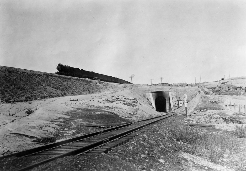 Tunnel 3 was completed in 1917 as part of adding a second track between Emory and Wahsatch. The tunnel was replaced by an adjacent cut in 1943, and both portals remain today. The westbound train is on the original 1868-1869 track. (Union Pacific Photo)