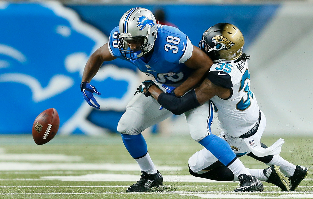 . Jacksonville Jaguars cornerback Demetrius McCray (35) forces  Detroit Lions running back George Winn (38) to fumble in the second half of a preseason NFL football game at Ford Field in Detroit, Friday, Aug. 22, 2014. (AP Photo/Rick Osentoski)