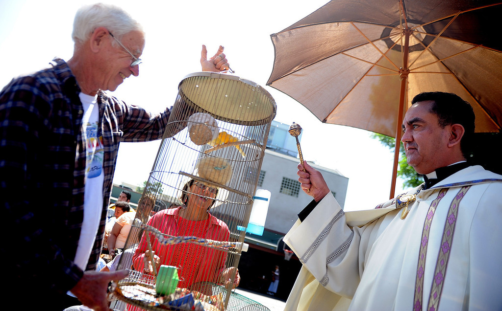 . Father Paul Sustayta, right, blesses canaries Elvis and Evira with their owner Don Bima, left, during the traditional Blessing of the Animals at St Andrew Church School on Saturday, March 30, 2013 in Pasadena, Calif. 