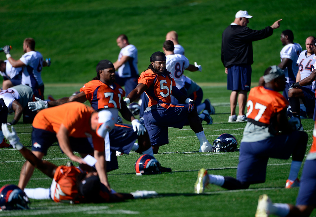 . The team moves in to stretching sequences at the start of practice. The Denver Broncos football team gets in their final day of practice during training camp at Dove Valley  on Friday, Aug. 15, 2014. (Photo by Kathryn Scott Osler/The Denver Post)
