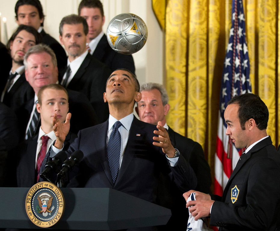 . Los Angeles Kings coach Darryl Sutter, second from right, Los Angeles Galaxy forward Landon Donovan, right, and others, watch as President Barack Obama bounces a soccer ball off his forehead during a ceremony honoring the Stanley Cup hockey champion Los Angeles Kings and the Major League Soccer champion LA Galaxy, Tuesday, March 26, 2013, in the East Room of the White House in Washington. (AP Photo/Manuel Balce Ceneta)