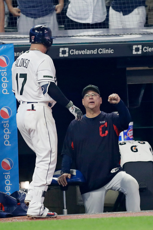 . Cleveland Indians manager Terry Francona, right, congratulates Yonder Alonso after Alonso hit a two-run home run in the fourth inning of a baseball game against the Houston Astros, Saturday, May 26, 2018, in Cleveland. Edwin Encarnacion scored on the play. (AP Photo/Tony Dejak)