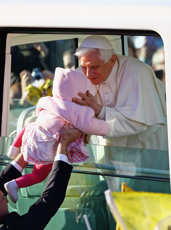 . Pope Benedict XVI has announced that he is to resign on February 28, 2013 GLASGOW, UNITED KINGDOM - SEPTEMBER 16: Pope Benedict XVI kisses a young child as he arrives for the Papal Mass at Bellahouston Park on September 16, 2010 in Glasgow, Scotland. Pope Benedict XVI is conducting the first state visit to the UK by a Pontiff. During the four day visit Pope Benedict will celebrate mass, conduct a prayer vigil as well as beatify Cardinal Newman at an open air mass in Cofton Park. His Holiness will meet The Queen as well as political and religious representatives.  (Photo by Jeff J Mitchell/Getty Images)