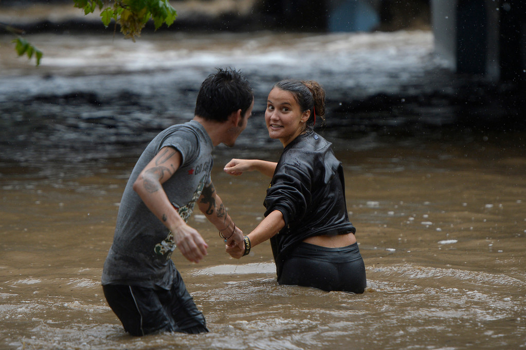 ". BOULDER, CO. - SEPTEMBER12:  University of Colorado student Laura Schubart jokes with Chris Cavazos before attempting to cross a flooded underpass along Boulder Creek in Boulder, CO September 12, 2013. When she returned to safe ground she said, ""that current is stronger than the ocean and I\'m from California.\"" Record-breaking rain turned normally quiet creeks into raging, brown torrents that swept through Boulder on Thursday, flooding homes, swamping cars and closing roads and schools. (Photo By Craig F. Walker / The Denver Post)"