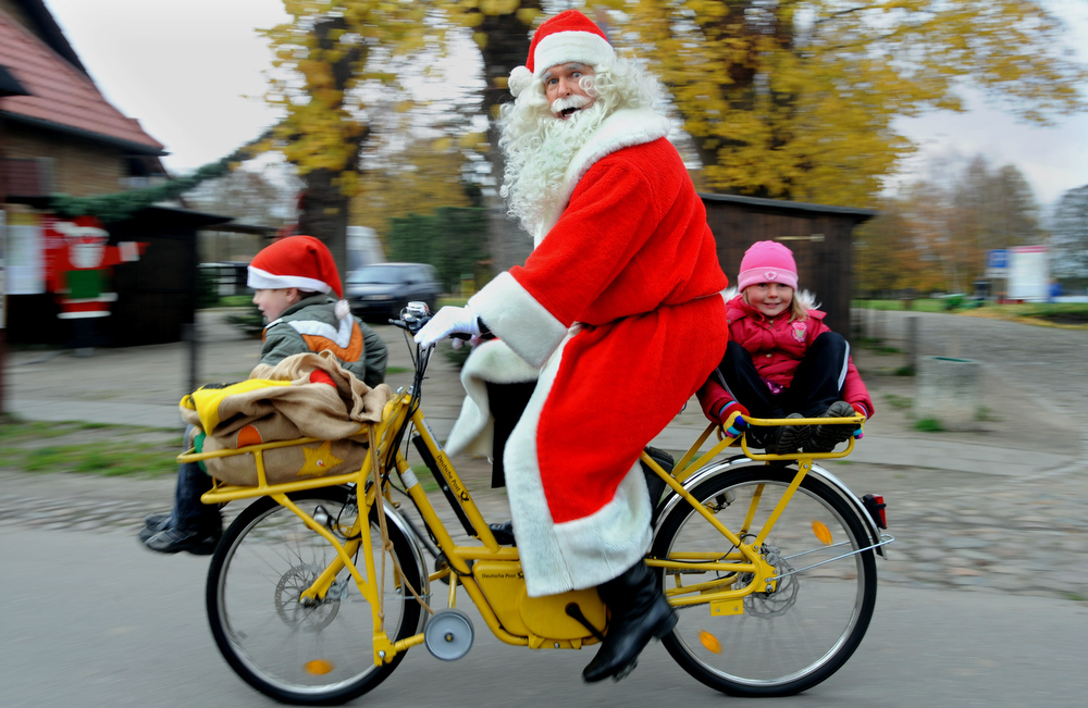Description of . A Santa Claus on his bike carries two kids through the village of Himmelpfort (Heaven's Gate) about 100 kilometres north of Berlin, Germany. There he opened a famous German Christmas mail office. Last year about 280.000 children wrote their wishes to the address