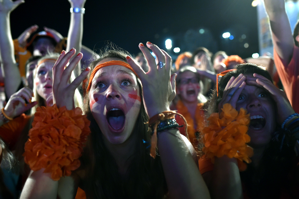 . Fans react to the live projection of the quarter-final match between Netherlands and Costa Rica on Copacabana Beach in Rio de Janeiro on July 5, 2014, during the FIFA World Cup 2014 in Brazil.  (YASUYOSHI CHIBA/AFP/Getty Images)