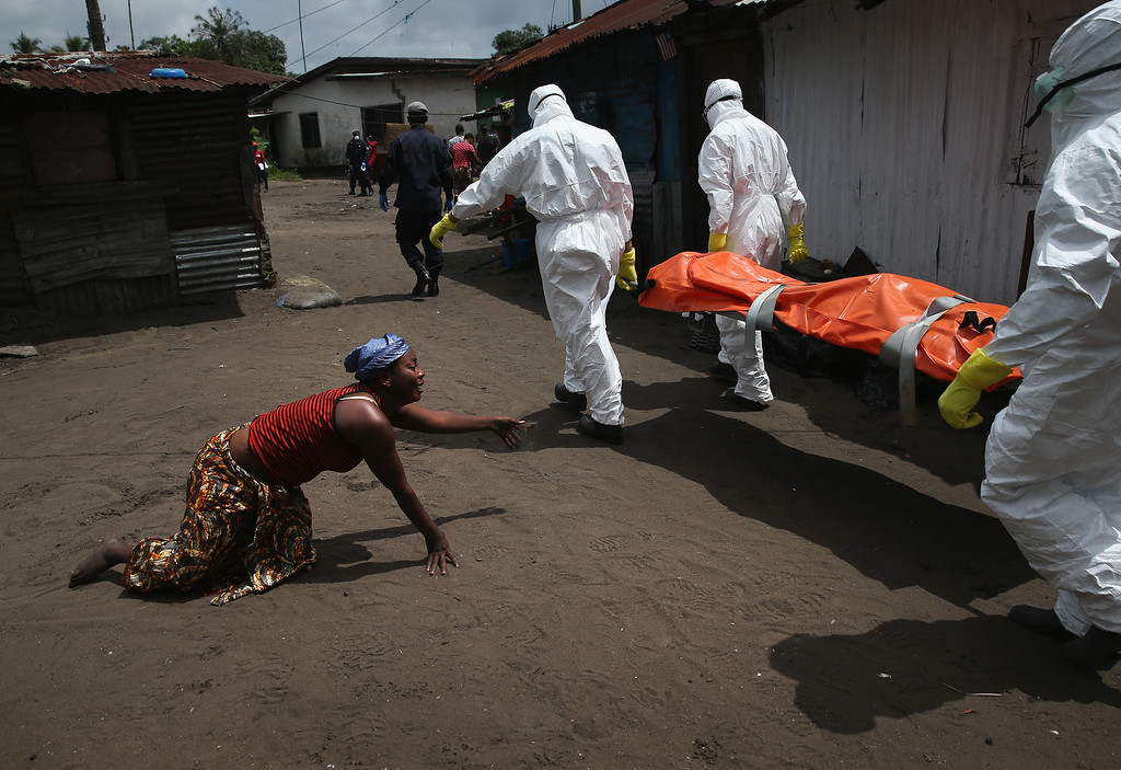 . EBOLA: A woman crawls towards the body of her sister as Ebola burial team members take her sister Mekie Nagbe, 28, for cremation on October 10, 2014 in Monrovia, Liberia. Nagbe, a market vendor, collapsed and died outside her home earlier in the morning while leaving to walk to a treatment center, according to her relatives. The burial of loved ones is important in Liberian culture, making the removal of infected bodies for cremation all the more traumatic for surviving family members. The World Health Organization says the Ebola epidemic has now killed more than 4,000 people in West Africa. (Photo by John Moore/Getty Images)