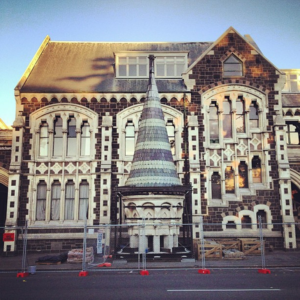 Christchurch past and present, an Arts Centre building with one of its towers resting on the sidewalk #chch