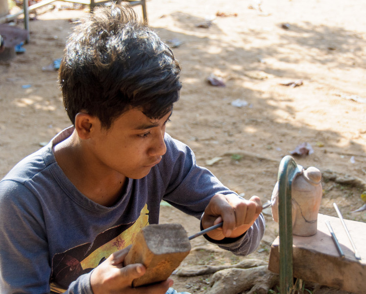 A stone carver at the temple Bakong. This boy was an apprentice stone carver. He was making a carving of the head of the great king Jayavarman VII. We purchased a finished head from him for $15.