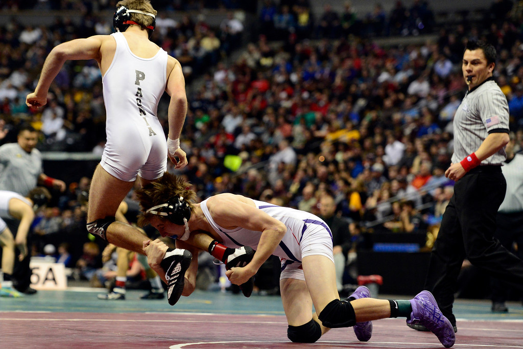 . DENVER, CO - FEBRUARY 23: Paonia 120-poumder Jesse Reed jumps as Stetson Loader shoots en route to Reed winning 7-5 in the class 2A final during the Colorado State High School Wrestling Championships. The state\'s top wrestlers squared off in four classes in front of a near-capacity crowd at the Pepsi Center. (Photo by AAron Ontiveroz/The Denver Post)
