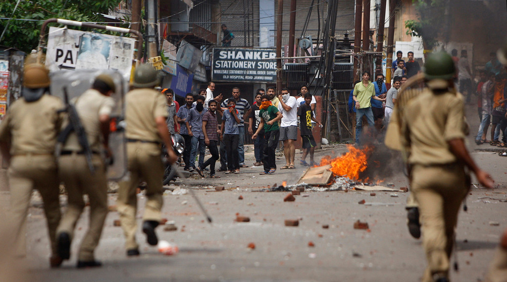 . Indian policemen chase Hindus protesting against the state government after rival communities clashed in Kishtwar, in Jammu, India, Saturday, Aug. 10,2013. Indian forces fired warning shots Saturday to enforce a curfew and to push angry people back into their homes in Kishtwar, in the Indian portion of Kashmir where clashes between Muslims and Hindus during Eid celebrations killed at least two people and injured another 24.(AP Photo/Channi Anand)