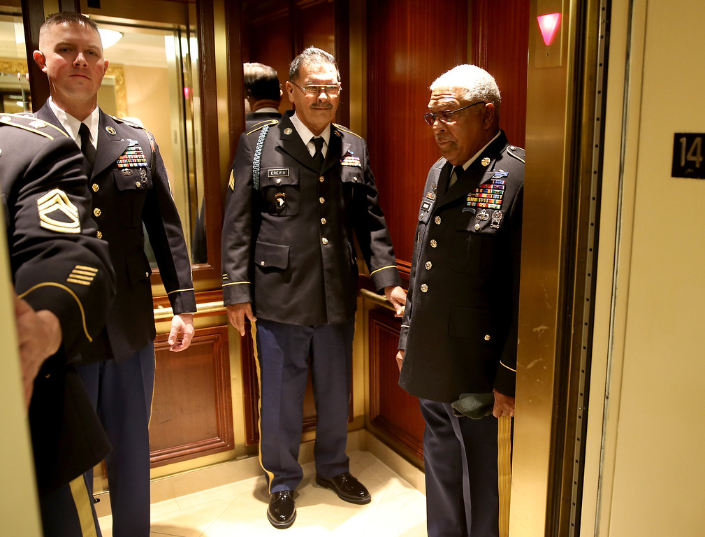 . U.S. Army Specialist Four (Ret.) Santiago J. Erevia (C) and U.S. Army Staff Sgt. (Ret.) Melvin Morris, both of whom are Vietnam War veterans, stand in the elevator togther as they make their way to the White House on March 18, 2014 in Washington, DC. (Photo by Joe Raedle/Getty Images)