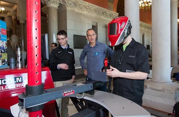 04/24/19 Wesley Bunnell | Staff A Student-Manufacturer Connection Fair was held on Wednesday at the State Capitol Building connecting over 500 students and dozens of Connecticut companies to explore careers in advanced manufacturing. Goodwin College's Assistant Professor in Welding Technology Jason Sagaci, center, explains the workings of a welding training simulator to Xavier High student Spencer Thompson as he tries the simulator while classmate Aidan Muldoon looks on.