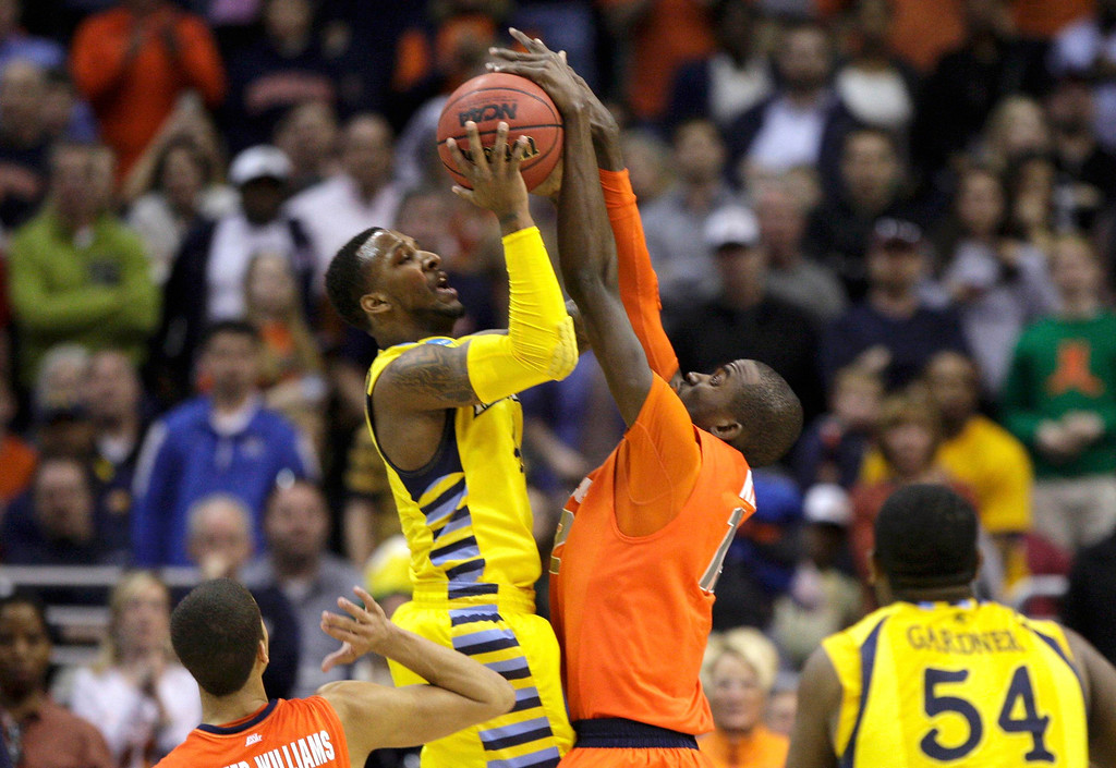 . Syracuse Orange center Baye Keita (R) blocks Marquette Golden Eagles guard Todd Mayo during the first half in their East Regional NCAA men\'s basketball game in Washington, March 30, 2013. REUTERS/Jonathan Ernst (UNITED STATES  - Tags: SPORT BASKETBALL)