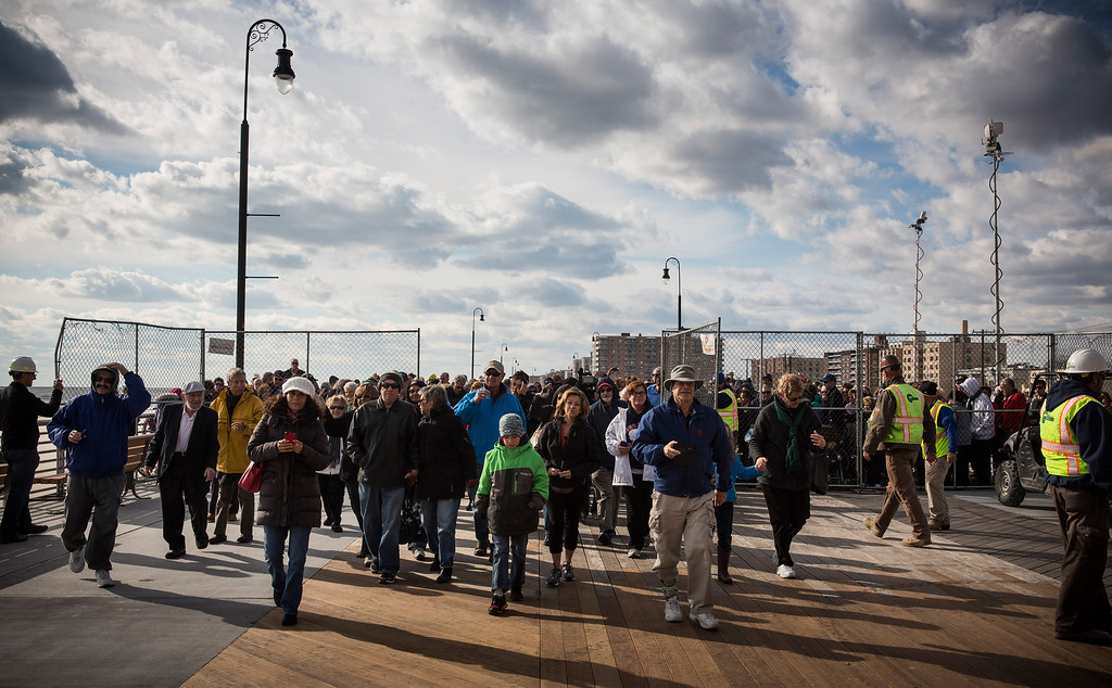 . LONG BEACH, NY - OCTOBER 25:  Citizens walk onto the boardwalk during a ceremony to officially reopen the boardwalk on October 25, 2013 in Long Beach, New York. The boardwalk was severely damaged by Superstorm Sandy last year, which killed 285 people and caused billions of dollars in damage. Long Beach\'s new boardwalk is made of Brazilian hardwood and is estimated to have a lifespan of 30-40 year; the previous boardwalk was only scheduled to last  three to seven years.  (Photo by Andrew Burton/Getty Images)