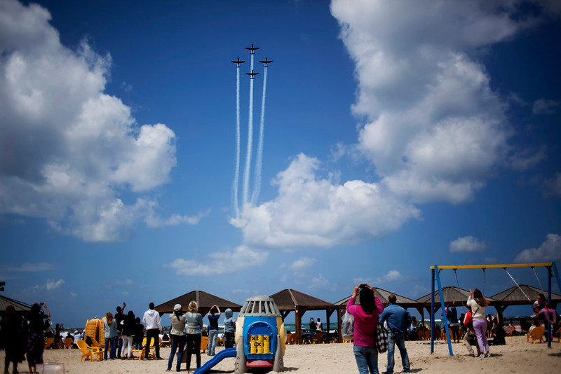 . People take photographs of an air show during Independence Day in Tel Aviv, Tuesday, April 16, 2013. Israel is celebrating its annual Independence Day, marking 65 years since the founding of the state in 1948. (AP Photo/Ariel Schalit)